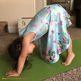 Young girl on a green yoga mat in a down dog pose