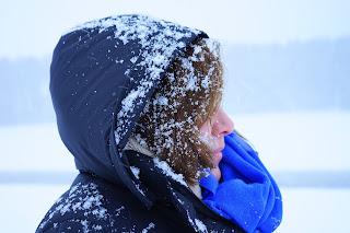 Garota com casaco azul escuro com a cabeça cheia de neve