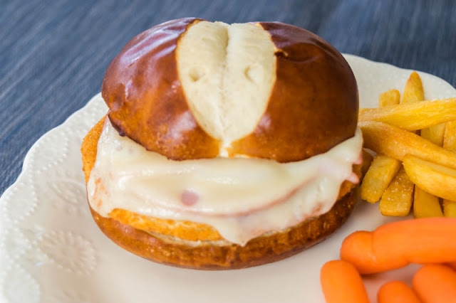 chicken cordon bleu sandwich with carrots and fries