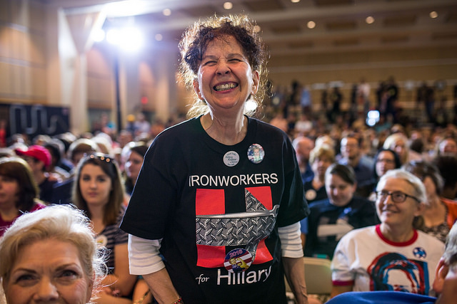 image of a middle-aged woman who appears to be white, standing up in the middle of a crowd at a Hillary rally, wearing a t-shirt that says IRONWORKERS FOR HILLARY and smiling broadly