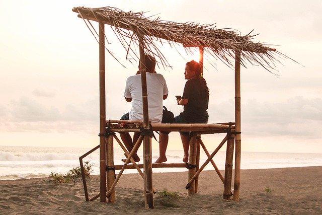 dua orang sedang mengobrol ditepi pantai