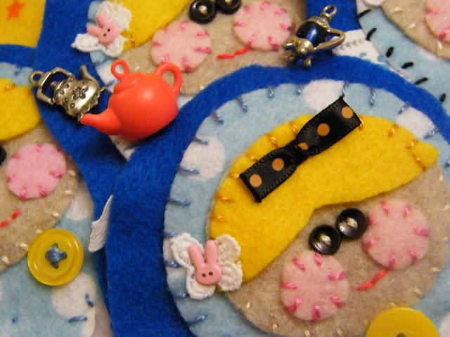 Handwerk met borduursels en frutsels erop genaaid, gezichten, theepotjes, knoopjes, vrolijk.