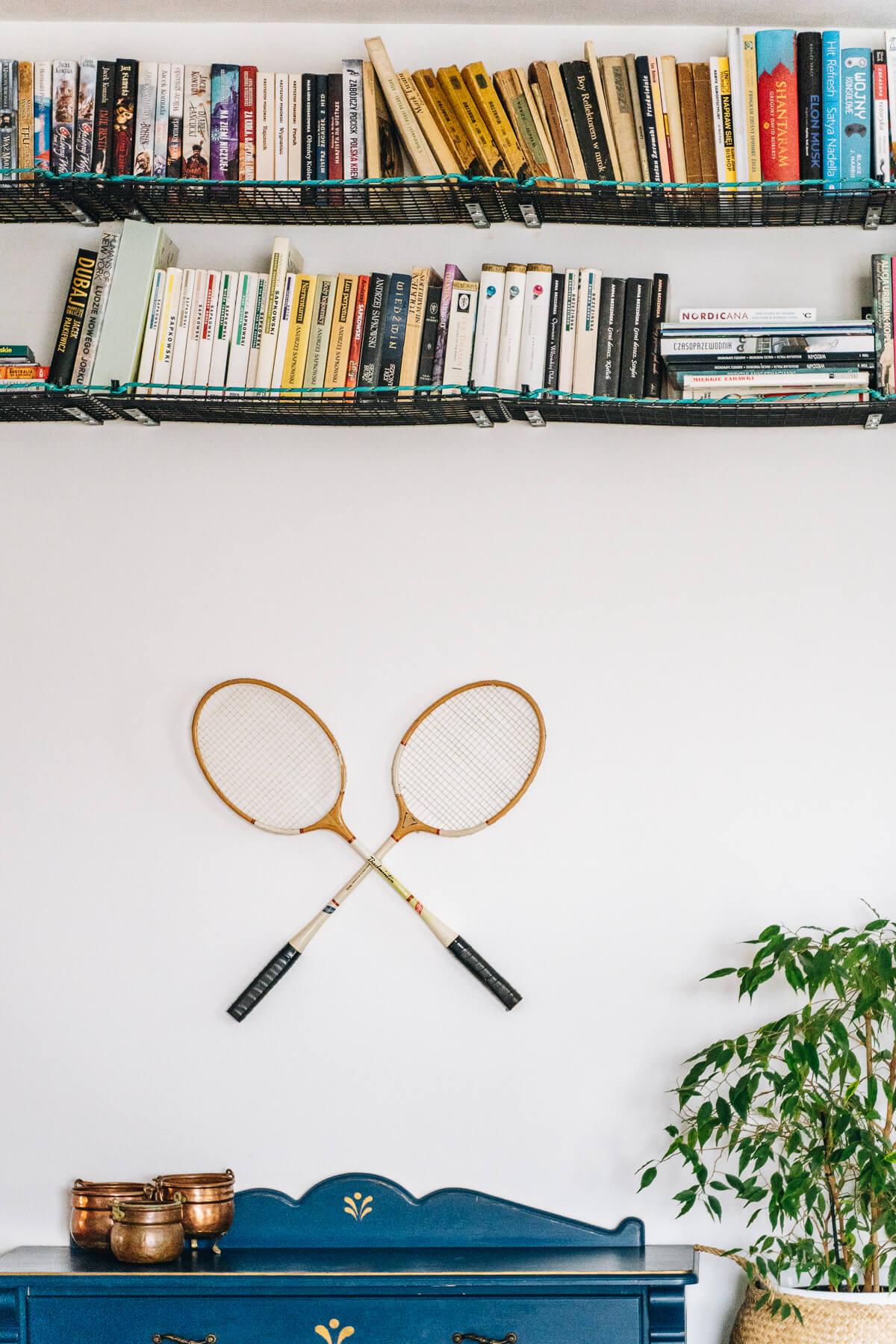 Fragment ściany ze starymi drewnianymi rakietami do badmintona jako dekoracją i półką na książki