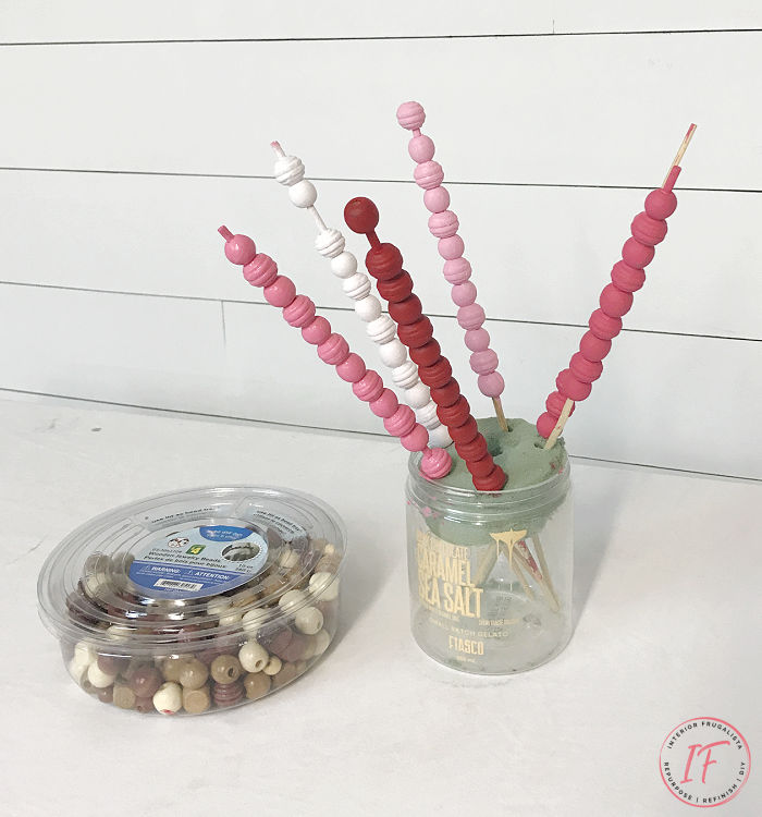 A budget-friendly DIY wooden bead garland painted a pretty gradient pink ombre for Valentine's Day made with a string of dollar store wooden beads.
