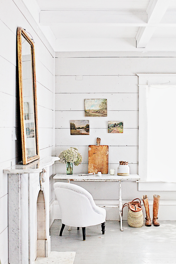 Farmhouse style decor with white shiplap, vintage chair, French fireplace and French farmhouse market basket. Dreamy Whites.