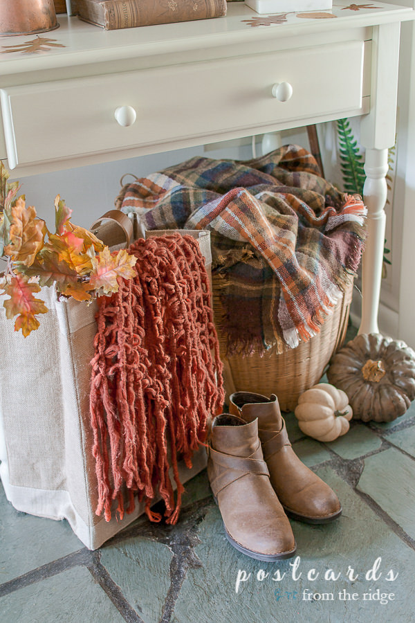 plaid blanket in a large basket with boots on the floor
