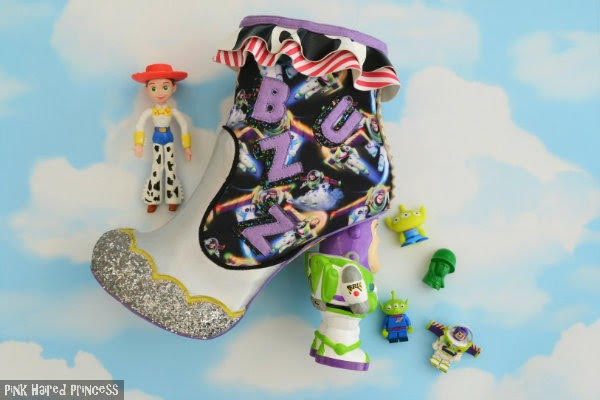 buzz lightyear ankle boot lying on cloud background with small toy story toys strewn around