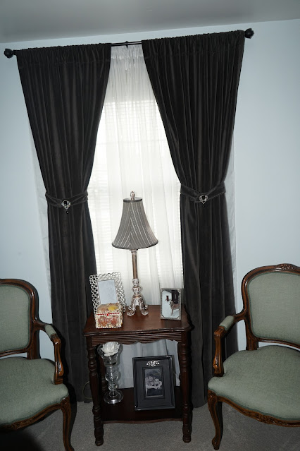 Velvet curtains with tie backs, French chairs, and antique table