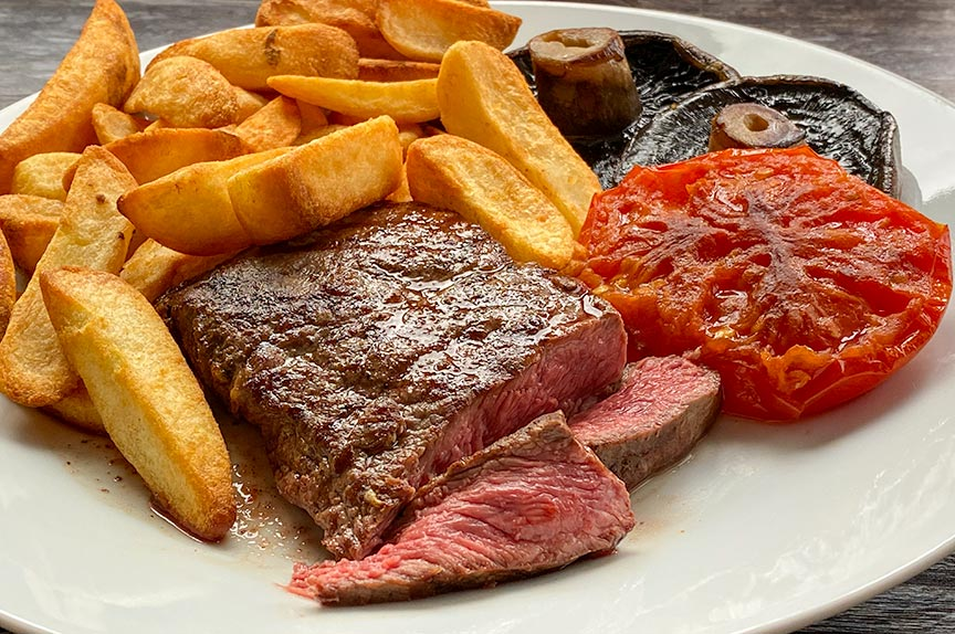 Flat iron steak with chips, mushrooms and tomato
