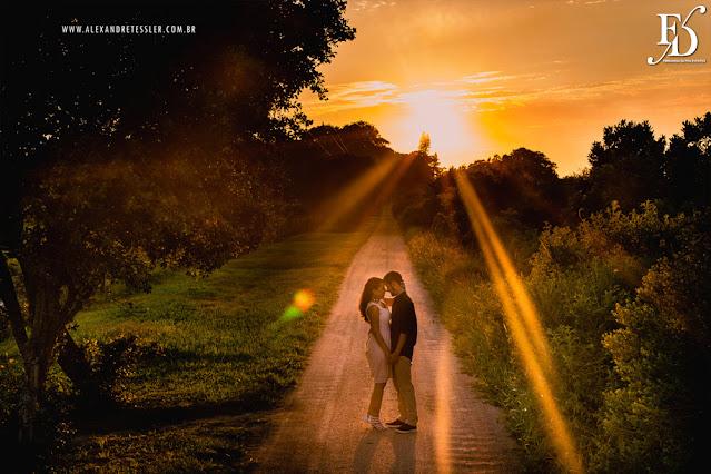 ensaio pré-wedding de renata e bruno e a filha alexia no campo com o por do sol e a lagoa emoldurando a cena e o amor deles