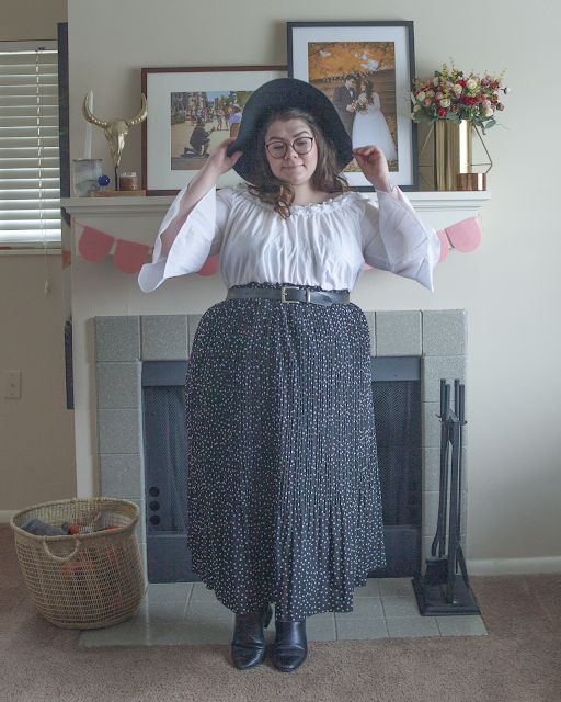 An outfit consisting of a black wide brim hat, white off the shoulder blouse tucked into a black and white dotted and pleated maxi skirt and black chelsea boots.