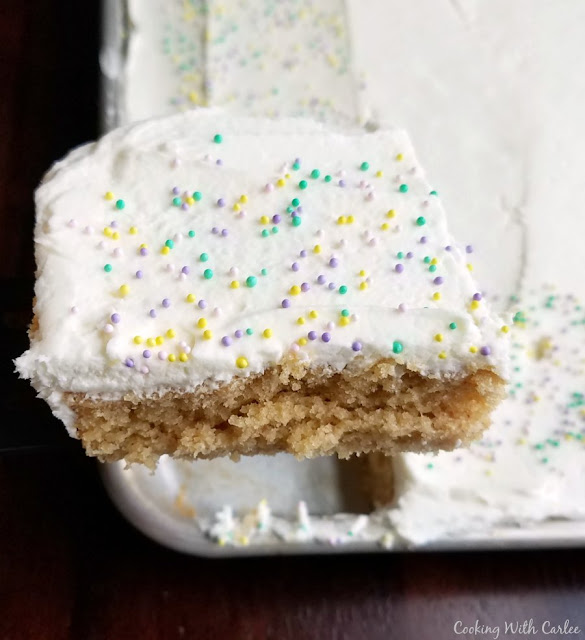 slice of peanut butter sheet cake with white chocolate buttercream and sprinkles on top