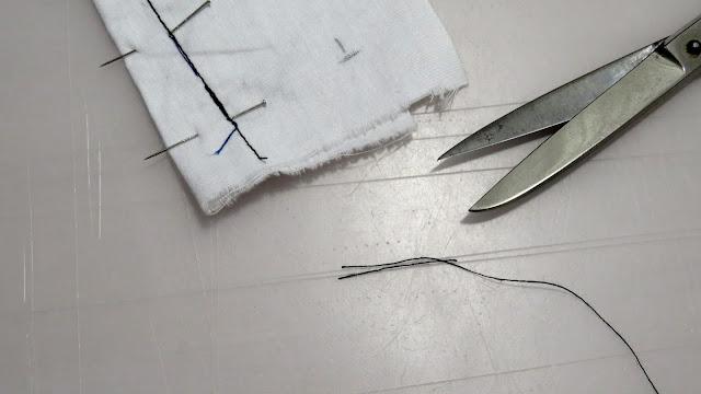 Hilos cortados del inicio de costura de la pinza