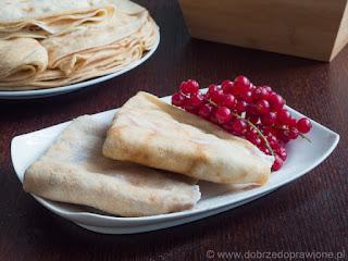 Naleśniki z serem na białym talerzu udekorowane czerwoną porzeczką