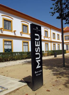 fachada de um edifício branco e uma placa de museu