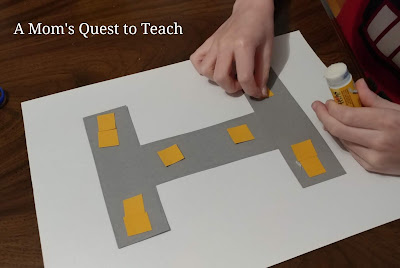 gluing squares onto letter I construction paper