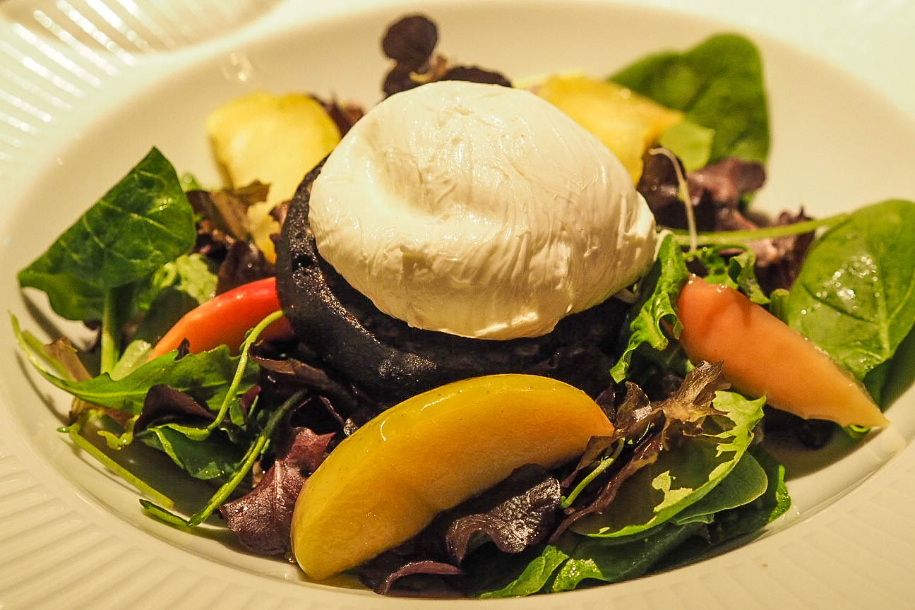 Poached egg on black pudding with apples and salad leaves