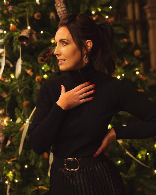 woman in black outfit in front of christmas tree