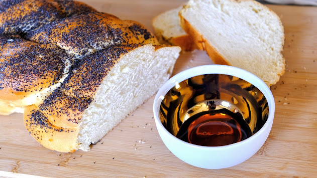 Challah bread with maple syrup on a chopping board