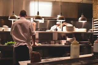 hombre de espaldas cocinando en la cocina de un restaurante