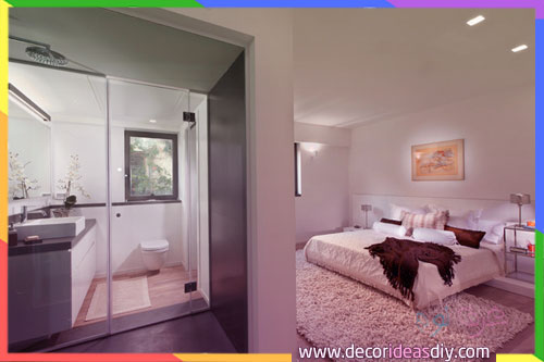 غرفة نوم تتوفر على كبائن حمامات زجاج خاصة بالحمام