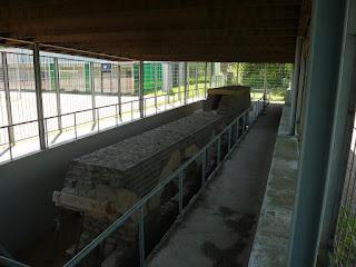 Ein altes Steinfundament, in dem auf Säulen gebaut ein kleiner, steinerer Tunnel verläuft. Alles von einem Zaun und einem Dach umgeben