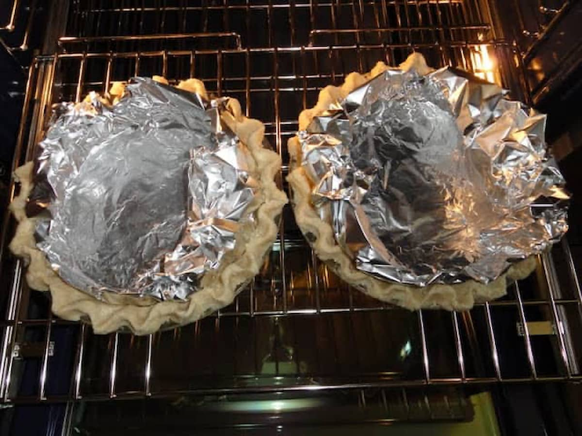2 Flaky Pie Crust Shells lined with Foil placed inside oven to bake.