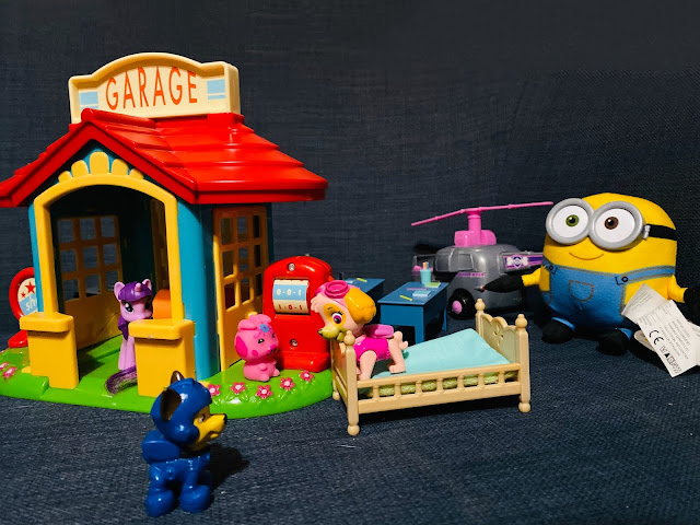 A multicoloured toy world including a Happyland Garage with a my little pony peering out, skye from Paw Patrol standing on a bed and talking to Chase, some Peppa Pig desks in the background next to Skye's helicopter and a soft minion toy