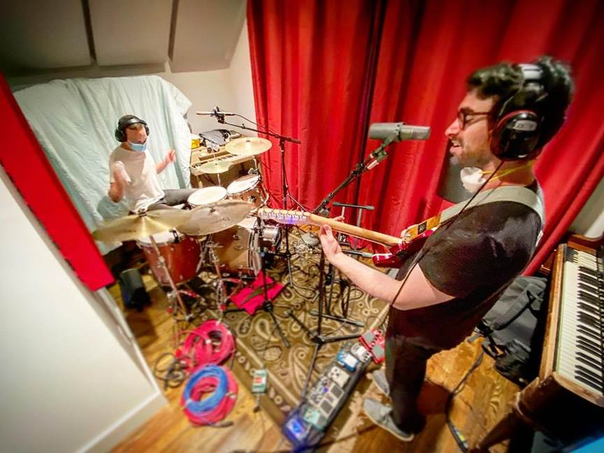 Jesse with guitar and headphones and Charlie on the drums inside the recording studio with