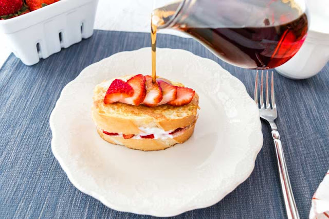 strawberry stuffed french toast topped with strawberries and maple syrup
