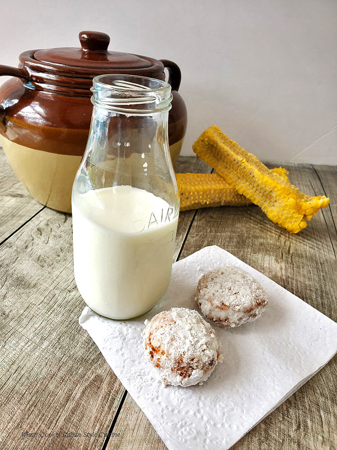 this is an old fashioned dairy bottle of milk with corn fritters on a napkin there is a bean pot and shucked corn on the cob in the photo
