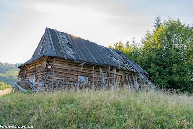 Drewniany budynek opodal kurnej chaty