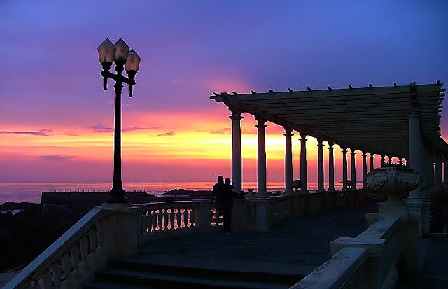 Casal apreciando o pôr do sol na Pérgola do Porto