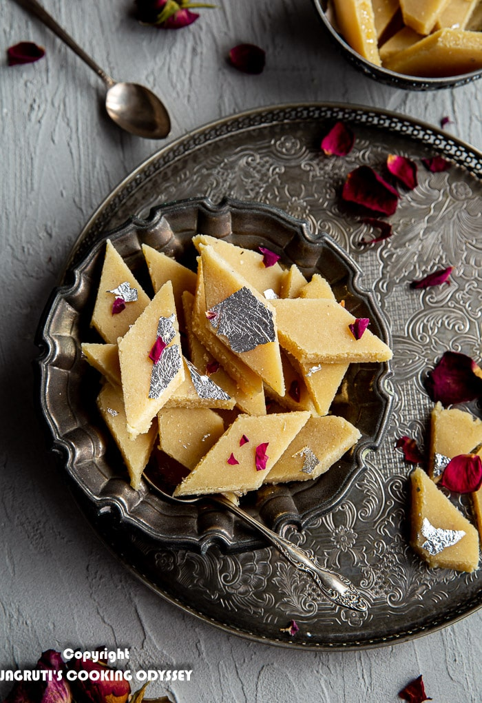 Over head shot of no added sugar badam katli in instant pot served in a metal bowl and garnished with red dried rose petals