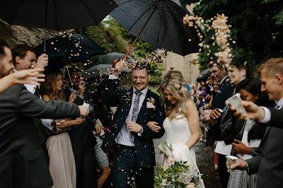 Novios saliendo del lugar de la ceremonia rodeados de invitados que les lanzan confetti