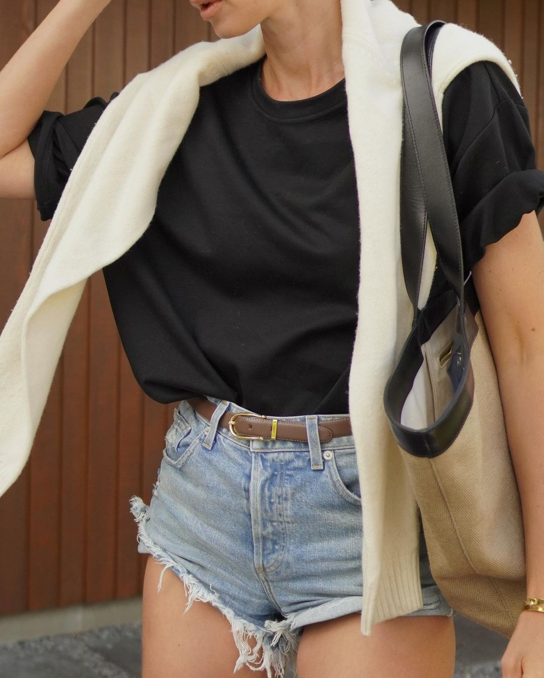 Short Denim Shorts Outfit Idea — Transitional style from Anouk Yve ina black t0shirt, cut off shorts, tote bag, thin belt and cream sweater over the shoulder