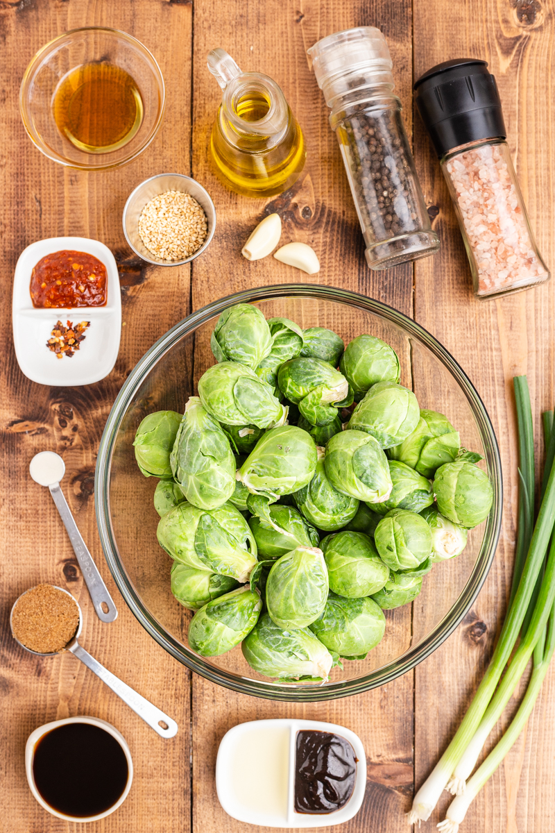 Overhead photo of the ingredients needed to make Kung Pao Brussels Sprouts on a wooden table.