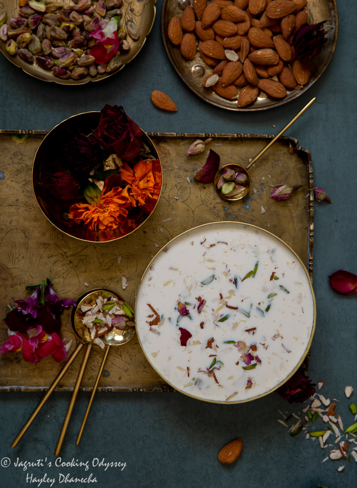 Traditional creamy basundi served in a brass bowl topped with slivered nuts and dried rose petals