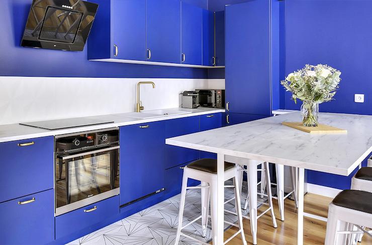 Cocina abierta al salón con mobiliario azul y encimera blanca.