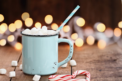 a mint colored cocoa mg with marshmallows and a stripes white and mint colored straw on a table with marshmallows and candy canes and lights in the background