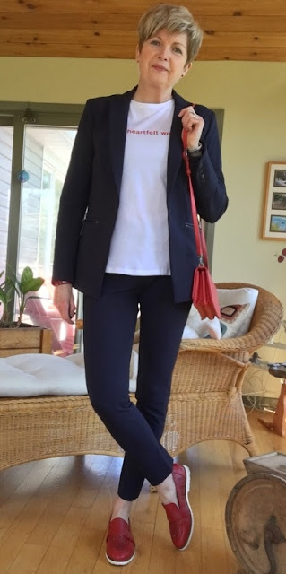 woman in red shoes, navy pants suit, white tee with red lettering and red shoulder bag