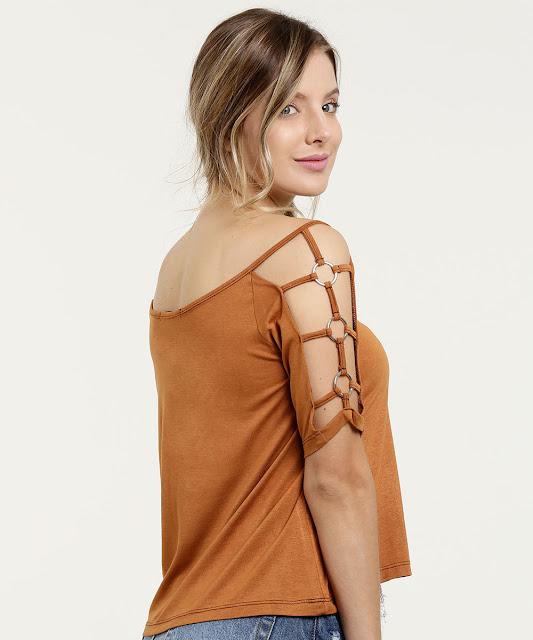 Possui decote redondo, manga curta com vazado, tiras finas, argolas, acabamento e costura no tom