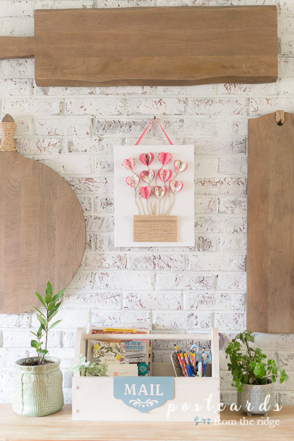 white brick wall with wooden cutting boards and 3-D paper heart wall art
