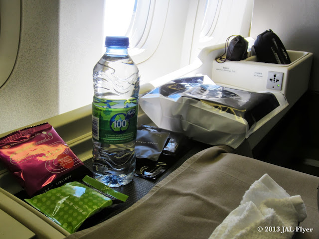 JAL First Class trip report on JL005 - Cabin attendants handed out bottled water and First Class amenity kits after first meal service