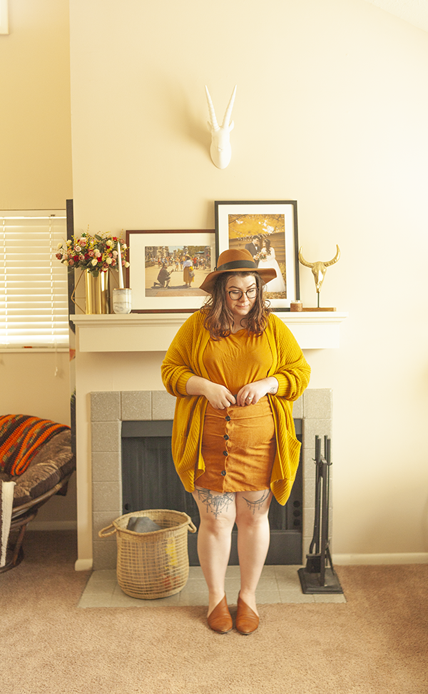 An outfit consisting of a brown panama hat, oversized chunky mustard yellow cardigan, yellow brown top tucked into a brown button down mini skirt and brown d'orsay flats.