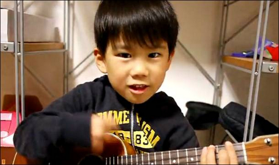 A cute Asian boy plays a ukulele and sings.