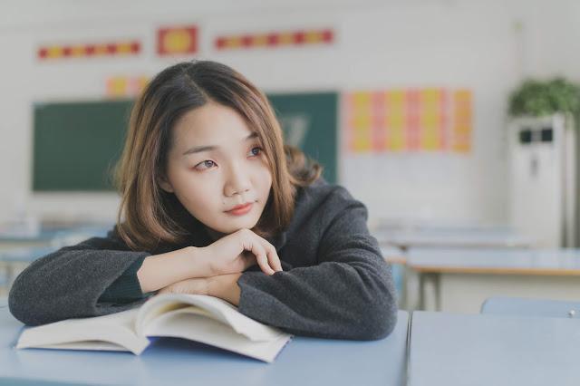 Menina coreana na sala de aula olhando para o lado