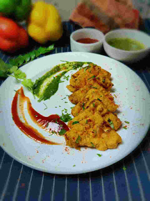 Serving paneer pakora with green chutney and tomato ketchup in a garnished plate