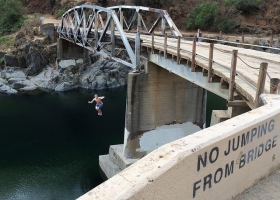 A boy disobeys the sign of not jumping from the bridge.