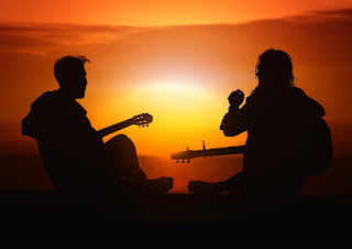Two people sat on the ground with guitars, silhouetted against a setting sun.